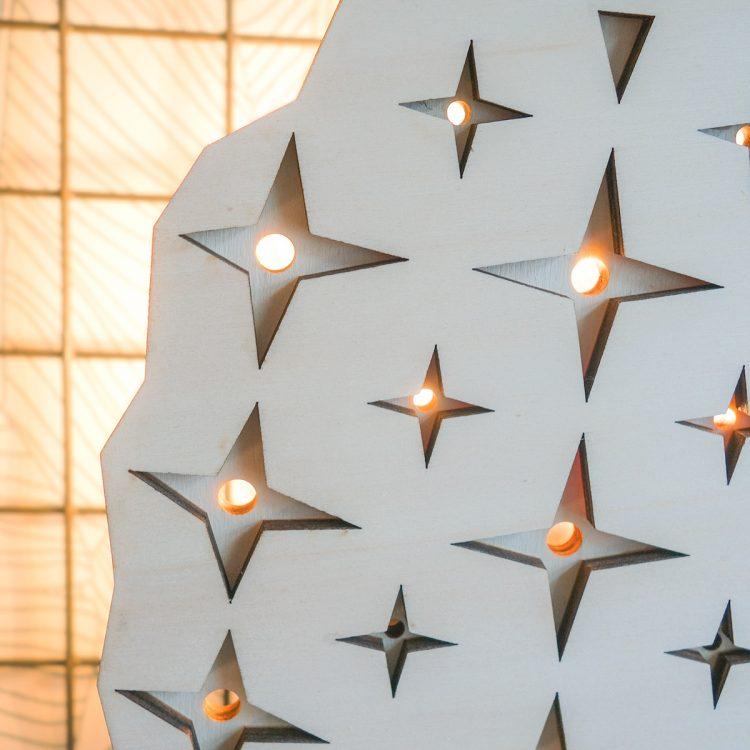Detail van houten ananaslamp. Het licht schijnt door de gaatjes van de lamp, dit geeft een sfeervol effect aan je interieur.