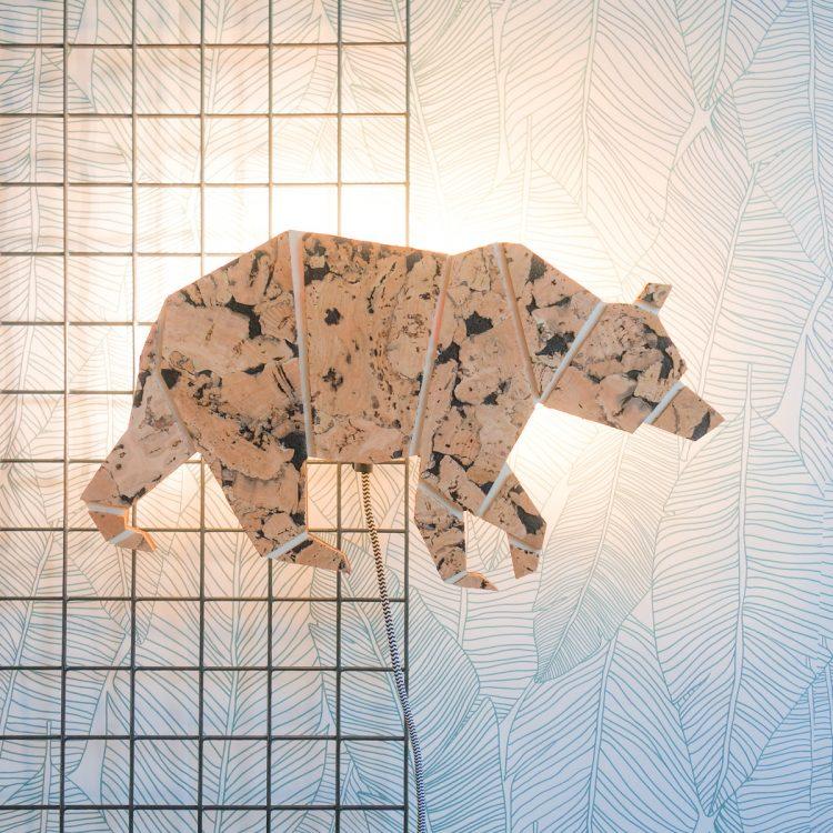 Wandlamp beer (origami vorm) van duurzaam hout en kurk, waarbij de lamp aan is. De lamp heeft een gekleurd strijkijzersnoer.