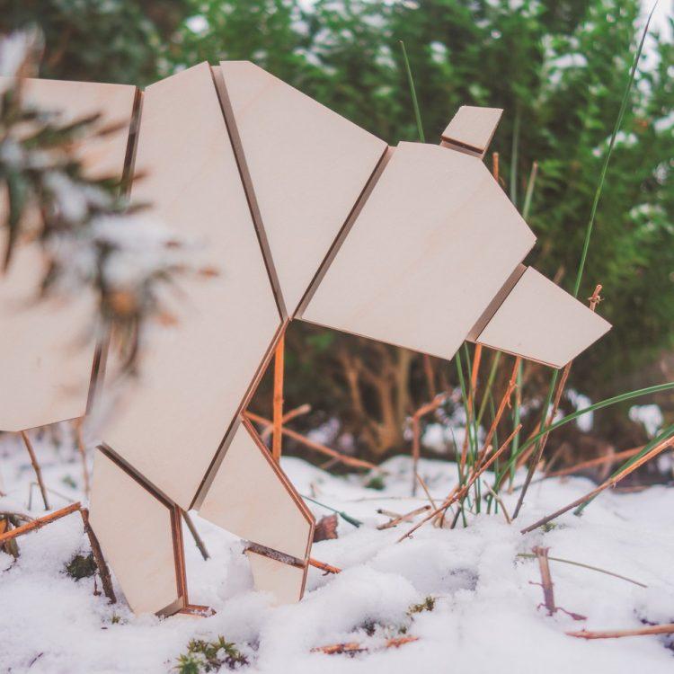 Houten berenlamp in de natuur. De beer heeft geometrische vormen en staat in de sneeuw.