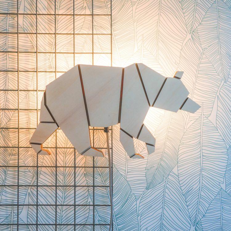 Houten berenlamp met luxe strijkijzersnoer. De lamp verspreid een sfeervol licht tegen de muur en heeft geometrische origami vormen.