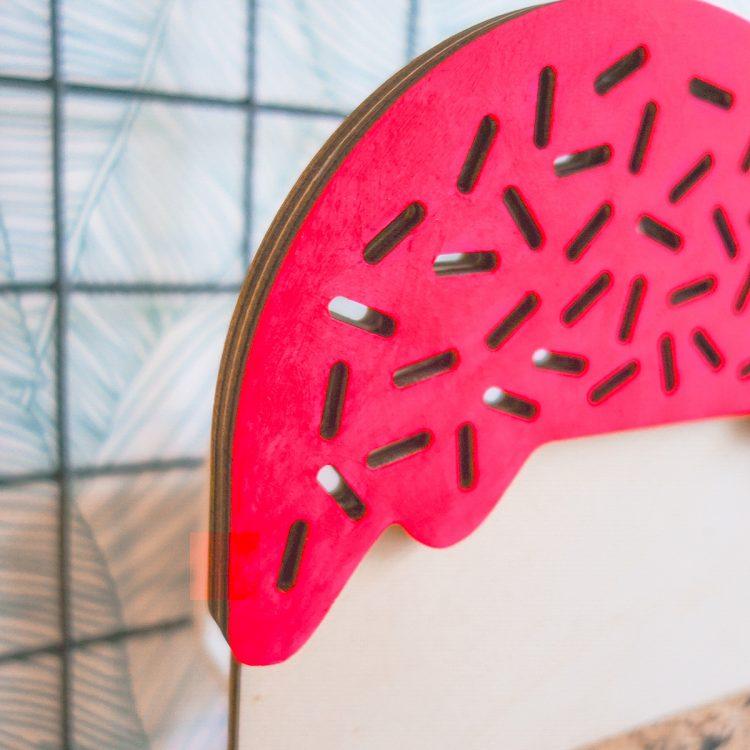 Detail van houten lamp in de vorm van een ijsje. De bovenkant heeft een fluor roze topping met sprinkles, waardoor het licht schijnt.