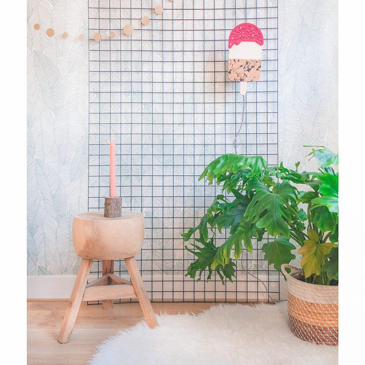 Sfeerbeeld van roze ijsjeslamp in een interieur. De lamp is gemaakt van de natuurlijke materialen hout en kurk en heeft een speels kleureffect.