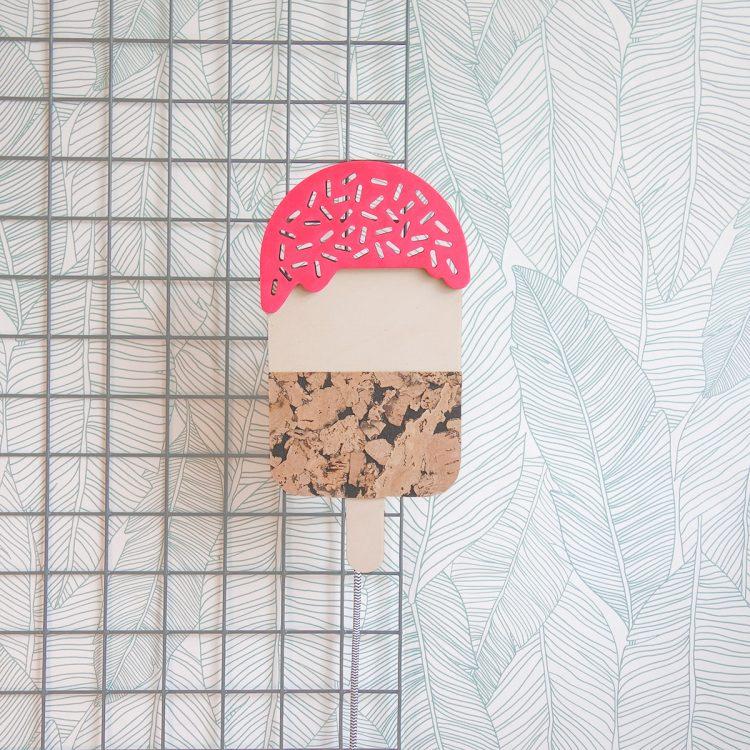 Vooraanzicht van houten ijsjeslamp met roze bovenkant. De lamp is gemaakt van hout en kurk en geeft een speels effect aan het interieur.