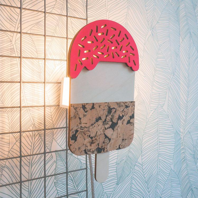 Houten ijsjeslamp waarbij het licht sfeervol door de gaatjes van de sprinkles van het ijsje valt. Het ijsje heeft een fluor roze topping.