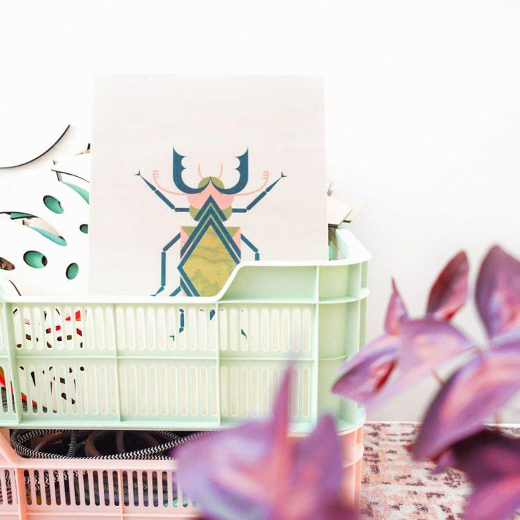 Sfeerfoto van houten poster met insect (vliegend hert) in interieur. Het insect bestaat uit grafische vormen.