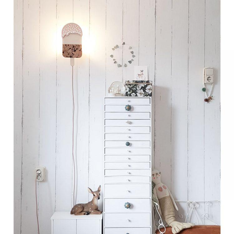 Ijsjes lamp van hout in de kleur zacht roze in interieur van meisjeskamer. Sfeerbeeld waarbij de lamp aan is.