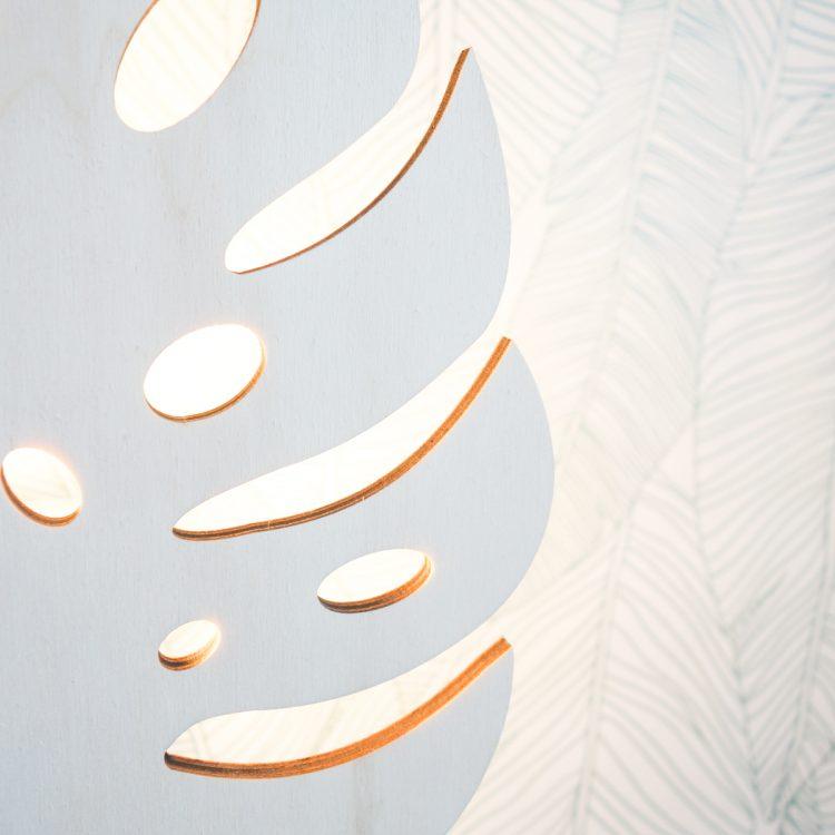 Detail van houten monstera verlichting (close-up). Het licht schijnt sfeervol door de openingen van het blad.