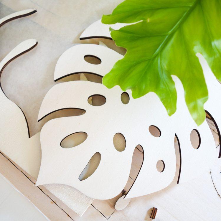 Houten monstera plantenblad op een tafel. Onderdeel van een lamp in de vorm van een blad.