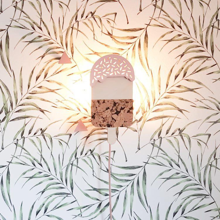 Roze ijsjes lamp van hout aan de wand, waarbij de lamp aan is. Het licht schijnt door de openingen (sprinkles) aan de bovenkant.