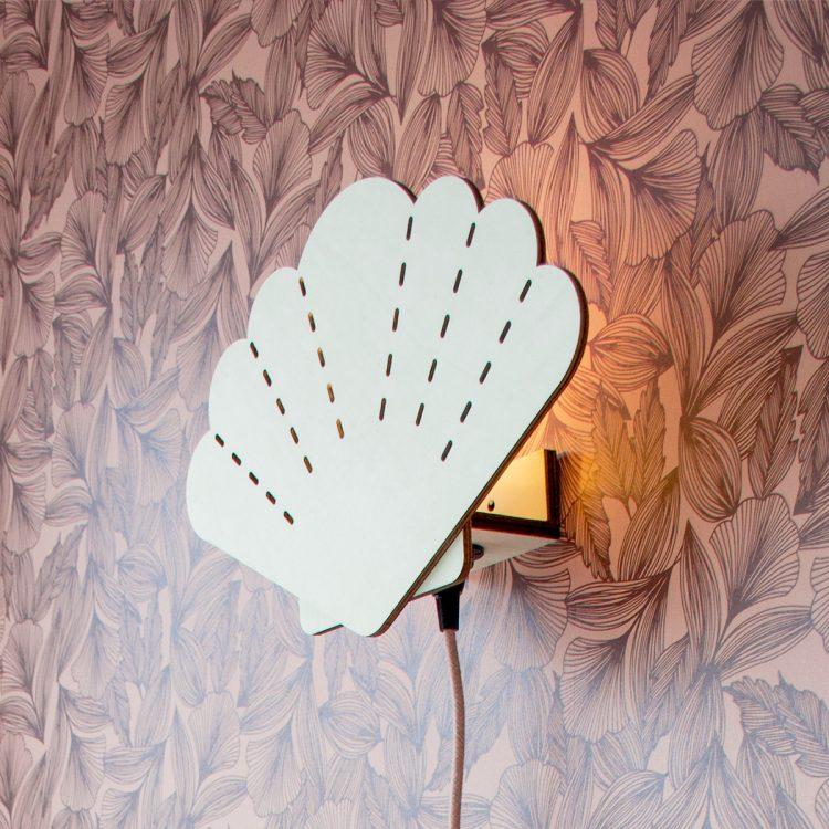 Zijaanzicht van een houten wandlamp in de vorm van een schelp. De lamp is aan en er schijnt sfeervol licht door de openingen van de lamp.