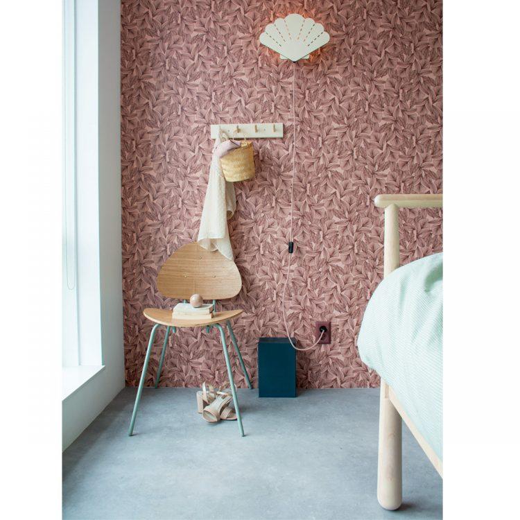 Houten schelp verlichting met gekleurd snoer in interieur. Sfeerbeeld van de schelp wandlamp in een slaapkamer met roze en licht houten tinten.